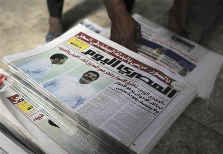 A shopkeeper sells copies of the daily newspaper Al-Masry Al-Youm with pictures of ousted Egyptian President Mohamed Mursi in white prison u