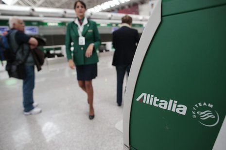 An Alitalia worker walks near an Alitalia auto check-in machine at Fiumicino airport in Rome October 11, 2013. REUTERS/Tony Gentile