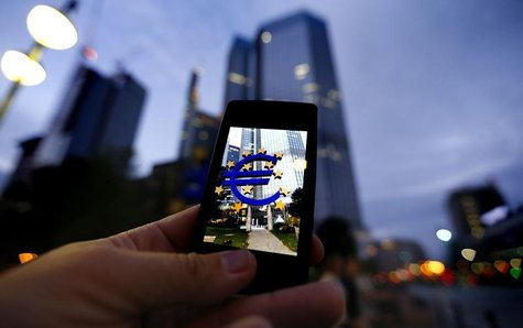 A passerby uses his smartphone to take a picture of the euro sign landmark in front of the headquarters of the European Central Bank (ECB) i