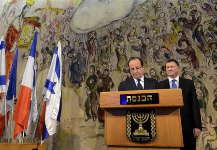 Yuli Edelstein (R), Speaker of the Knesset, Israel's parliament, stands behind France's President Francois Hollande as he signs the guest bo