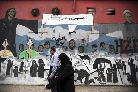 People walk in front of a mural depicting victims of the Egyptian uprising at Mohamed Mahmoud street near Tahrir Square in Cairo, November 1