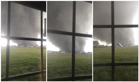 An active tornado is seen through a window as it touches down in Washington, Illinois on November 17, 2013, in this combination of three still images captured from a video courtesy of Anthony Khoury.