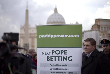 A man holds an advertisement for Paddy Power, an Irish bookmaker, in front of St Peter's square, outside the Vatican February 12, 2013. REUT
