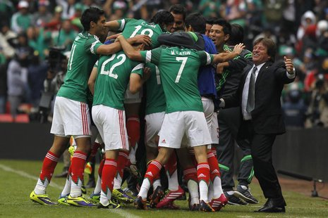 Mexico's coach Miguel Herrera (R) celebrates a goal with his players during their 2014 World Cup qualifying playoff first leg soccer match a