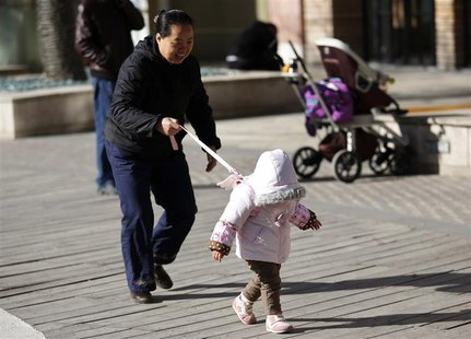 A woman holds onto a safety string attached to the back of a child at a shopping mall in Beijing, November 18, 2013. REUTERS/Kim Kyung-Hoon