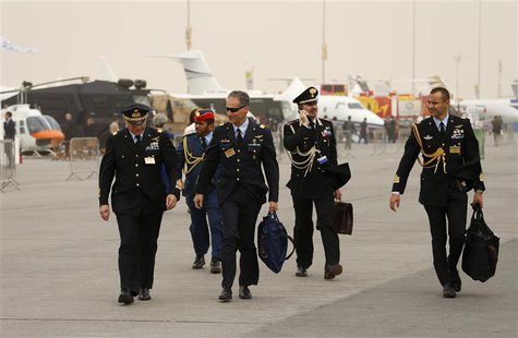 Military visitors walk during the sandstorm at the Dubai Airshow November 17, 2013. The flying display was cancelled due to the sandstorm. R