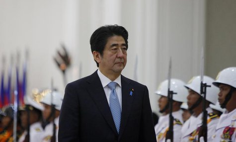 Japan's Prime Minister Shinzo Abe (C) inspects an honour guard at the Council of Ministers in central Phnom Penh November 16, 2013. Abe is i