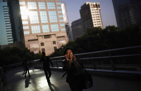 A woman talks on the phone as she walks along an elevated walkway in downtown Shanghai, November 18, 2013. REUTERS/Carlos Barria