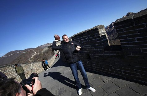 National Football League (NFL) Hall of Famer and former quarterback Joe Montana throws a football on the Mutianyu section of the Great Wall