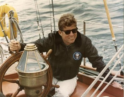 Former United States President John F. Kennedy sits onboard the U.S. Coast Guard yacht Manitou off the coast of Maine, in this handout image