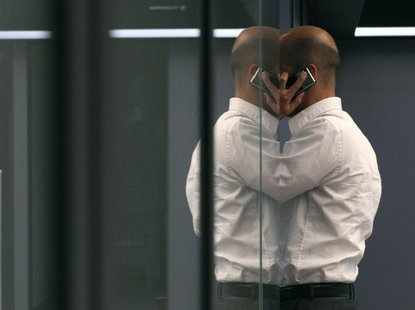 A bourse trader uses a cell phone during a trading session on the trading floor at Frankfurt's stock exchange August 2, 2011. REUTERS/Ralph