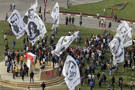 People wave banners depicting people who died in previous Egyptian revolutions around a monument, erected in honour of the victims, draped w