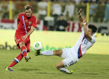 Park Jong-woo (R) of South Korea fights for the ball with Dmitry Tarasov of Russia during their international friendly soccer match at Al Wa