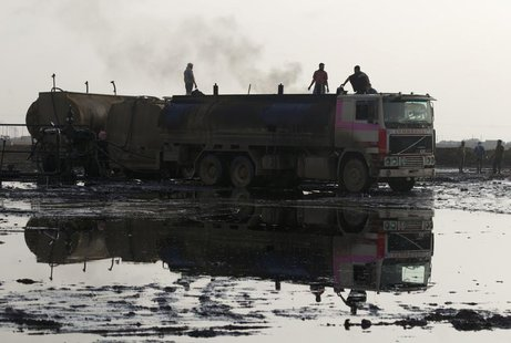 People stand on trucks near oil fields in Al-Rmelan, Qamshli province November 11, 2013. REUTERS/Stringer