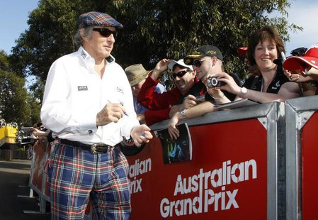 Former Formula One champion driver Jackie Stewart of Britain signs autographs as he arrives at the Albert Park circuit for the third practic