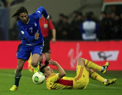 Georgios Samaras (L) of Greece controls the ball past Ovidiu Hoban of Romania during their 2014 World Cup qualifying soccer match in Buchare