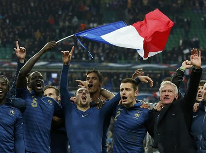 France's soccer team coach Didier Deschamps (R) and team mates celebrate after winning their 2014 World Cup qualifying second leg playoff so