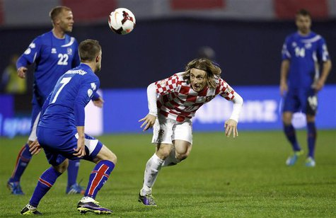 Croatia's Luka Modric (2ndR) challenges Iceland's Johann Gudmudsson (2ndL) and Eidur Smari Gudjohnsen (L) during their 2014 World Cup playof