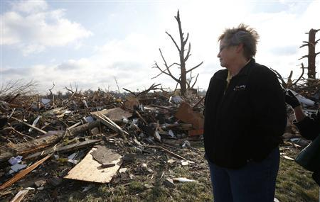 Pat Nelson looks out over the debris and destruction caused by a tornado that touched down in Washington, Illinois, November 18, 2013.  CREDIT: REUTERS/JIM YOUNG