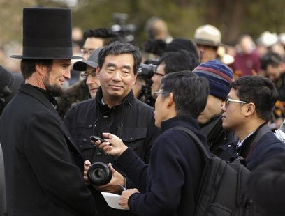 A re-enactor portraying U.S. President Abraham Lincoln (L) is interviewed by Japanese journalists at the Gettysburg National Cemetery in Pen