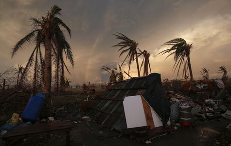 Part of a rainbow appears over the makeshift home of a family at the airport in the eastern Samar town of Guiuan November 20, 2013. REUTERS/