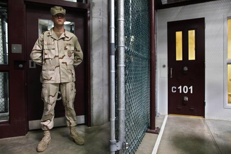 In this photo, reviewed by the U.S. military, a Guantanamo guard stands inside a doorway at Camp 6 detention facility at Guantanamo Bay U.S.