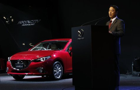 Mazda Motor Corp Chief Executive Officer Masamichi Kogai speaks next to the company's Axela (Mazda 3) compact car during a presentation at t