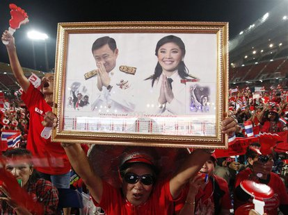 A red-shirted supporter holds up a pictures of Thailand's Prime Minister Yingluck Shinawatra and her brother Thaksin Shinawatra, during a ra