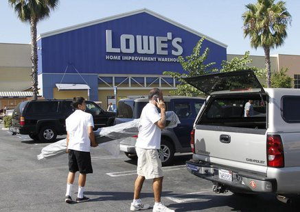 People load a roll of carpet into a vehicle at the Lowe's Home Improvement Warehouse in Burbank, California August 15, 2011. REUTERS/Fred Pr