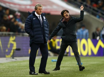 Germany's coach Joachim Loew (R) celebrates nex to England's manager Roy Hodgson after their international friendly soccer match at Wembley