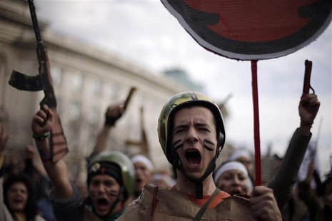 Protesting students wearing fake military uniforms shout anti-government slogans during a demonstration in front of Sofia University Novembe