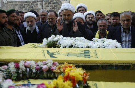 Lebanon's senior Hezbollah official Sheikh Nabil Qawouq (C) leads the prayer accompanied with Hezbollah parliament member Ali Ammar (centre