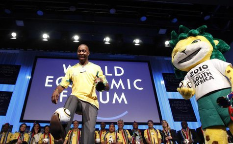 Former South Africa and Leeds United soccer player Lucas Radebe kicks a ball as he is joined by Zakumi, the 2010 World Cup official mascot d