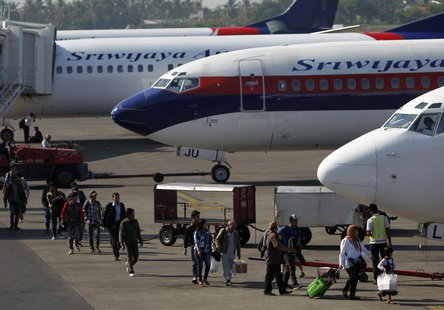 Passengers walk to their plane on the tarmac of Soekarno-Hatta airport in Jakarta, April 29, 2013. REUTERS/Beawiharta