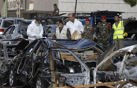 Forensic inspectors and Lebanese army soldiers examine the site of the two suicide bombings that occurred on Tuesday near Iran's embassy com
