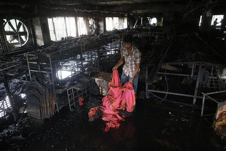 A garment worker inspects a factory belonging to Tung Hai Group, a large garment exporter, after a fire in Dhaka May 9, 2013. REUTERS/Andrew
