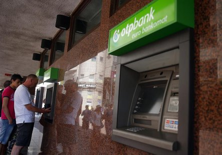 People withdraw money from an ATM at a branch of Hungary's largest lender OTP Bank in central Budapest July 24, 2013. REUTERS/Laszlo Balogh