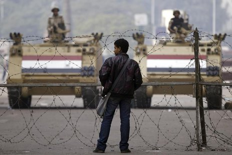 A man stands in front of a barbed wire fence set up by soldiers standing guard on armoured personnel carriers (APC) on Mohamed Mahmoud Stree