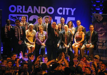 Orlando City SC president Phil Rawlins waves to his wife during a rally for a Major League Soccer official announcement for a expansion fran