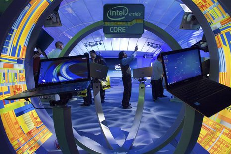 Gopi Sirineni (C) of San Jose, California takes a video of the Intel booth during the 2012 International Consumer Electronics Show (CES) in