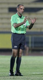 Referee Ali Sabbagh gestures during the AFC Cup soccer match between Kuwait's Al Qadsia and Yemen's Al Saqr in Kuwait City April 12, 2011. R