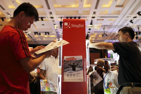 People look at brochures for deals on offer at the SingTel roadshow during the annual IT Show technology fair in Singapore March 10, 2012. R