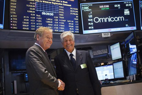 Omnicom Chief Executive John Wren (L) and Publicis Group Chairman and CEO Maurice Levy shake hands after announcing an agreement on their me