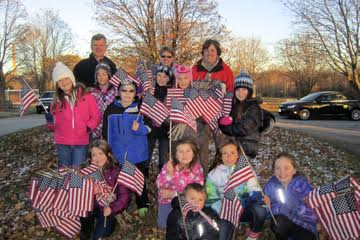 Holding some of the flags collected from the graves of veterans at Holy Cross Cemetery are (back row) Sexton Dan Ristow, parent, Deb Tryba, teacher advisor, Dawn Street.  (middle row) Elli Renzelmann, Gabrielle Bricko, Austin Tryba, Nevaeh Ehaney, Ava Wittstock, Ella Smith.  (front row)  Meghan Flook, Lillian Berry-Street, Hannah Hasenstein, Khloe Murphy, Landon Berry-Street.