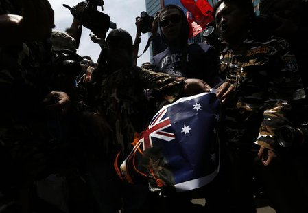 Protesters burn an Australian flag during a protest in front of the Australia embassy in Jakarta, November 21, 2013. Australia warned travel