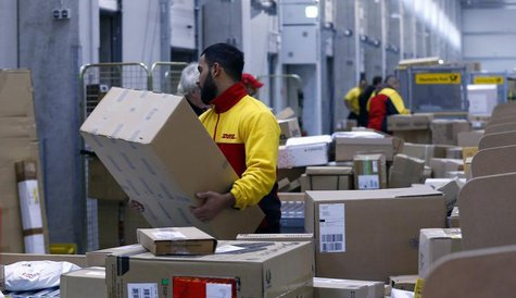 Workers load trucks with parcels at the new distribution centre of the German postal and logistics group Deutsche Post DHL in Berlin Novembe