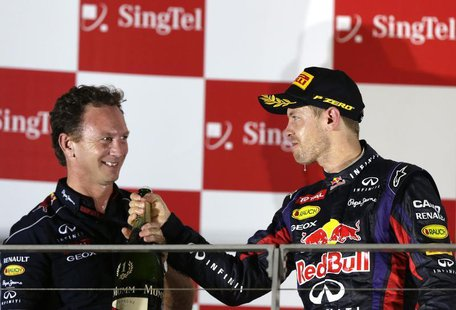 Red Bull team principal Christian Horner (L) celebrates on the podium with Red Bull Formula One driver Sebastian Vettel of Germany after Vet