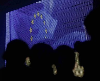 People are silhouetted against a screen showing the European Union flag as they attend a rally in support of euro integration in central Kie