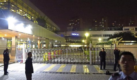 Police and security guards stand outside a gate of a Nokia factory during a protest of around one hundred factory workers in Dongguan, Guang