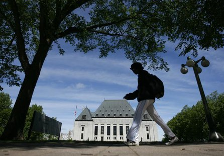 A woman walks past the Supreme Court of Canada in Ottawa May 7, 2010. REUTERS/Chris Wattie